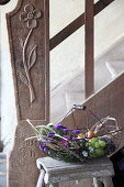 Basket of asters, grapes, pears and damsons for the harvest festival on stool