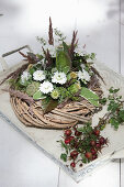 Wreath decorated with white asters, thistles and poppy seedheads next to posy of rose hips