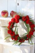 Roter Zinnienkranz aus Blütenköpfen und Rutenhirse auf Regal