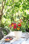 Zinnias, grasses and branches of dog rose in simple vase on garden table