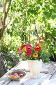 Strauss aus Zinnien, Gräsern und Wildrosenzweigen in schlichter Vase auf Gartentisch