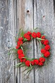 Wreath of red zinnias and switchgrass hung from board wall