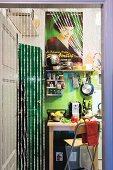 Blick durch Perlenvorhang in bunte Küche mit Filmplakat