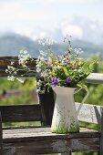 Wild flowers in white, painted jug on vintage garden bench