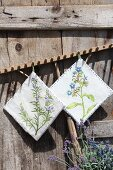 Hand-made pot holders with floral motifs run from wooden rake against rustic wooden wall