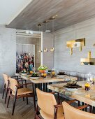 Set dining tables with stone wood marble tops in front of grey wood-clad wall