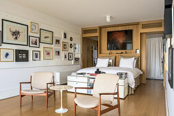 Two armchairs at foot of bed and gallery of pictures in bedroom