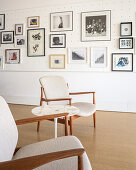 Two armchairs in front of gallery of pictures on perforated wall panel