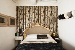 Bed with opulent headboard against patterned wallpaper