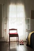 Cushion on red chair and red high-heeled shoes in front of window