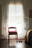 Roter Stuhl mit Kissen und rote High Heels vor dem Fenster