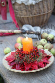 Candle in arrangement of rose hips and Virginia creeper leaves