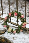 Romantic wreath of ivy leaves and roses in snow