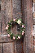 Romantic wreath of ivy leaves and roses hung from door handle
