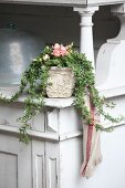 Arrangement of roses and ivy tendrils on vintage kitchen dresser