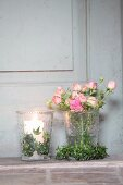 Romantic arrangement of ivy wreaths, roses and lit candles in glass vases