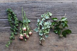 Various ivy tendrils and pink roses on rustic wooden surface