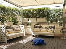 Blue turtle sculpture in front of outdoor sofas with scatter cushions on sheltered terrace