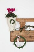 Cyclamen in stone vase and wreath of juniper twigs