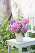 Hydrangeas of various colours in jug on white chair