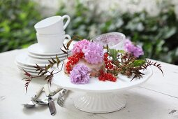 Small cake decorated with flowers and berries on table set for afternoon coffee