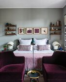 Two purple velvet armchairs at foot of bed with symmetrical accessories