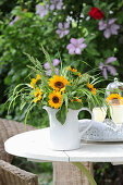 Sunflowers and ornamental grasses in jug on garden table