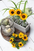 Sunflowers in glass bottles in wooden crate, candle lantern and wreath of sunflowers