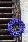 Wreath of cornflowers hung from vintage shutter