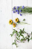 Cornflowers, sunflowers and clematis tendrils on white wooden surface