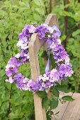 Heart-shaped wreath of hydrangea and phlox flowers on old wooden chair