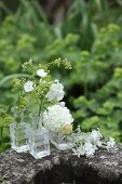 Various white flowers in small glass vases on edge of stone trough