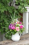 Luxuriant summer bouquet of pink flowers in jug