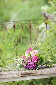 Luxuriant summer bouquet of pink flowers on wooden board
