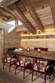 Classic chairs in rustic dining area below chunky wooden roof beams
