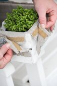 Decorating a wood chip basket with linen and decorative trim fixed with velcro