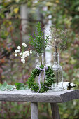 Small box wreath and twigs in two glass bottles