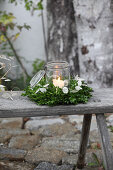 Lit candle in mason jar in wreath of box and honesty