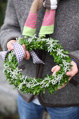 Wreath of box and santolina held in hands