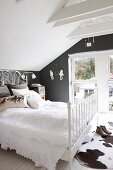 White blanket on bed and cowhide rug in attic room