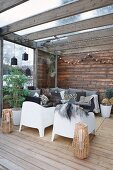 White outdoor armchairs in comfortable lounge area on roofed wooden terrace