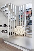 Designer lamp on landing with fitted bookcase in stairwell