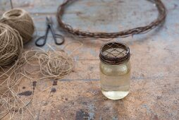 Jar of water with metal lid in front of parcel string and wire wreath