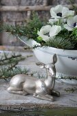 Silver doe ornament in front of arrangement of larch twigs and anemones in soup tureen