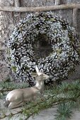 Doe ornament and larch twigs in front of wreath of pine cones and moss