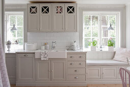 Bright country-house kitchen with grey panelled cabinets and windowseat