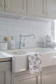 Tea towel draped over large ceramic sink in country-house kitchen with grey cabinets