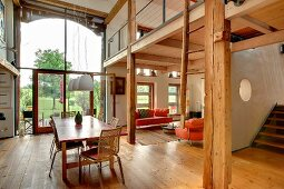Open-plan interior with rustic, modern atmosphere, gallery and glazed barn door