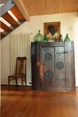 Collection of bottles on top of ornate, antique, ethnic wooden cabinet below staircase