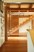 Modern wooden staircase in renovated period building with wood-beamed ceiling
